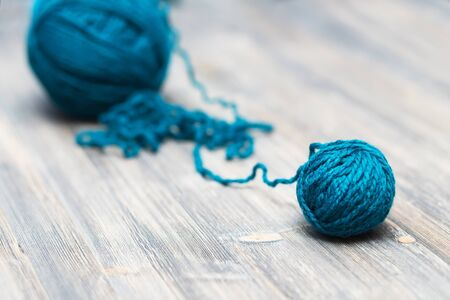 unwound: blue ball of wool on wooden background Foto de archivo