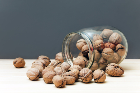 glycemic: Fresh walnuts in shells falling out of glass jar on wood table background Stock Photo