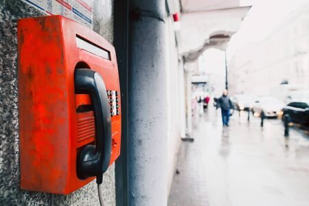 payphone: Red payphone on the wall. Background of the street