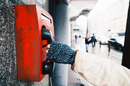 pay wall: Red payphone on the wall. Background of the street