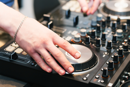 dancing club: hands on the DJ decks. Man makes music for dancing in the club. Mixer with vinyl record at party Stock Photo