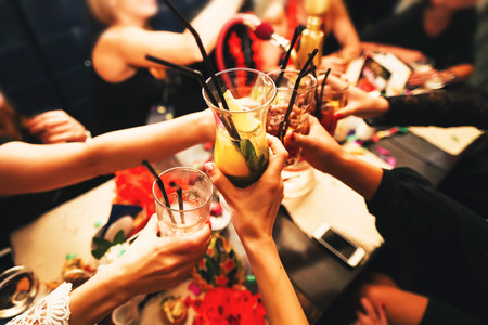 felicitaciones: Tintineo de vasos con alcohol y tostado, fiesta. Felicitaciones al evento. Amigos alegres del partido Foto de archivo