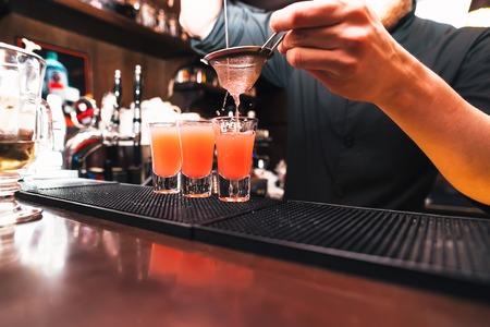 tomando alcohol: alcohol revuelo Barman. Proceso de preparación de un cóctel. Las bebidas alcohólicas en el vidrio Foto de archivo
