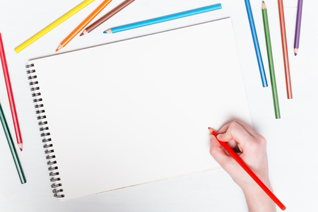 red pencil: Girl draws with colored pencils on paper. Mockup