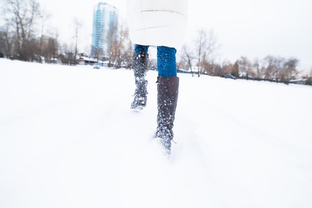 overtake: Girl running in the snow, late. Feet close-up
