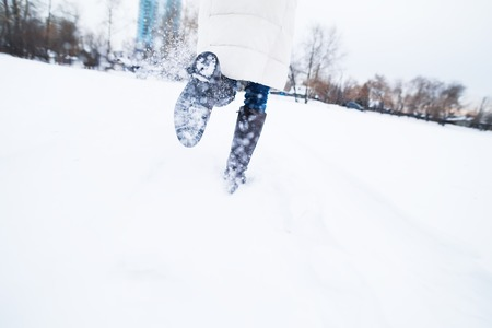 lateness: Girl running in the snow, late. Feet close-up