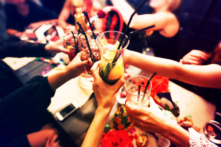 friends fun: Clinking glasses with alcohol and toasting, party Stock Photo