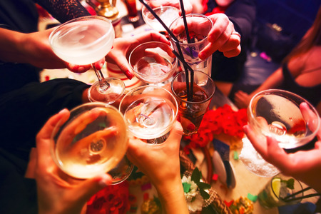 carnival party: Clinking glasses with alcohol and toasting, party Stock Photo