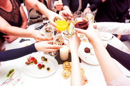 personas festejando: Tintineo de vasos con alcohol y tostado, fiesta. Felicitaciones al evento. Amigos alegres del partido Foto de archivo