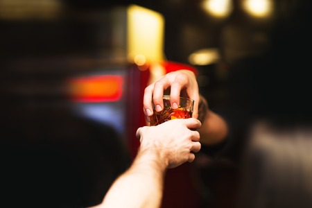 alcoholic beverage: Bartender gives ready cocktails. Alcoholic beverage in his hand Stock Photo