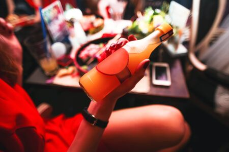 drunk girl: Woman holding a bottle of alcohol. On bar background
