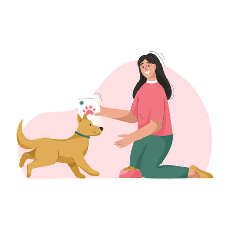 Woman is feeding dog. Owner takes care of puppy