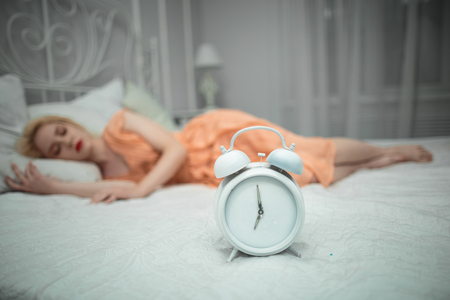 hands free device: She wants to sleep and sets the alarm. Stock Photo