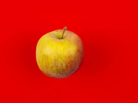 Fresh red juicy apple isolated on red background. High quality photo