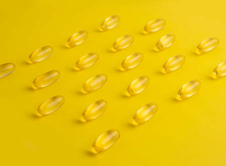 Fish oil omega 3 gel capsules on yellow background. Pills arranged in rows. High quality photo