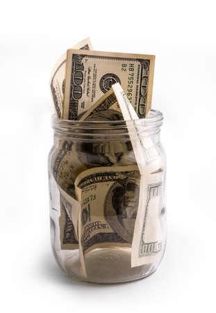 Keep money in glass jar - banka but not bank. Saving money or deposit program concept 免版税图像