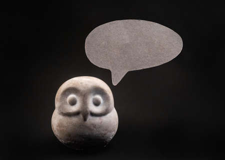 Wise owl gives useful advice. Night bird made of stone with paper message or thinking bubble on dark background