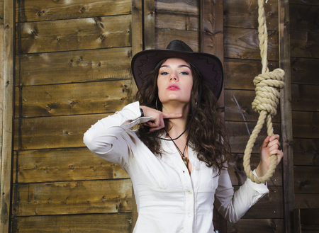 noose: the girl cowboy in the background of a wooden wall near the gallows shows head off