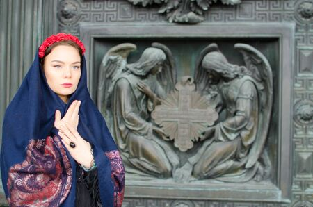 messengers of god: beautiful girl in a scarf near the Church on the background of angels Stock Photo