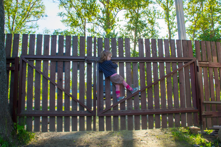 climbed: 4 years old girl climbed on the fence