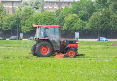 mows: Russia Saint Petersburg July 2016 tractor mows the grass Editorial