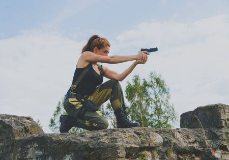 militaire sexy: redhead girl soldier is on one knee holding the gun. Banque d'images