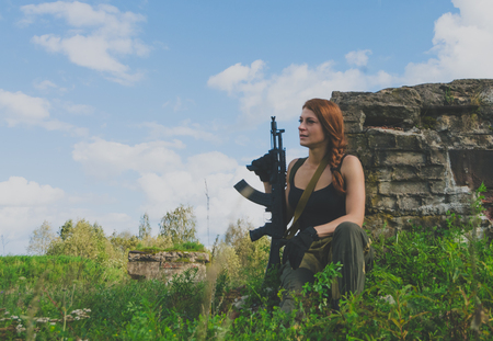 militaire sexy: redhead girl stands on the knee with a gun