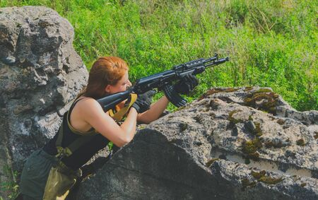 militaire sexy: beautiful military girl aiming a weapon based on the concrete cover.