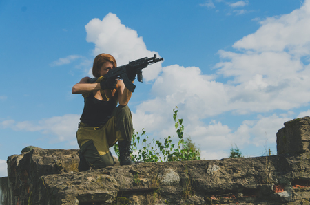 militaire sexy: girl soldiers take aim from the gun being on a hill