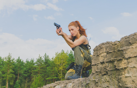 militaire sexy: redhead girl in tively to aim with a gun closeup