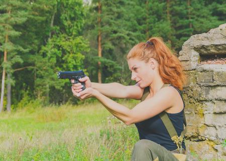militaire sexy: menace belle fille en uniforme avec une arme à feu Banque d'images