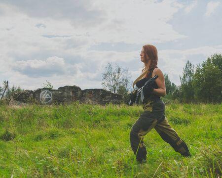 militaire sexy: fille dangereuse en uniforme avec des armes prêt à frapper