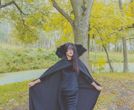 pitched: beautiful girl in a black mask in the woods pitched his cloak.