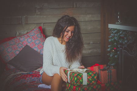 night before christmas: attractive girl in white sweater the night before Christmas parses gifts and smiles.