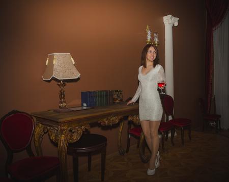 dans le hall du restaurant près de la table avec le téléphone belle fille avec un verre de vin. Banque d'images