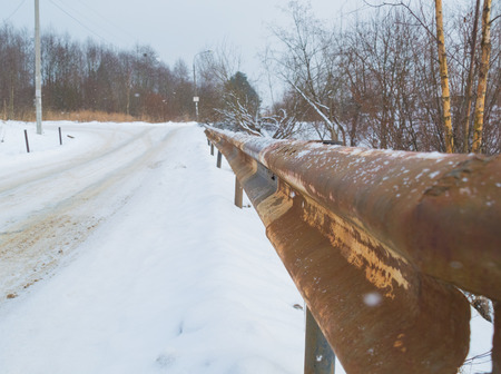 old rusty fence road bump in the winter.