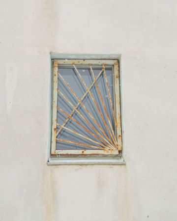 twin house: old rusty window and lattice. Stock Photo