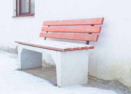 window bench: winter on the street bench at the wall with the window. Stock Photo