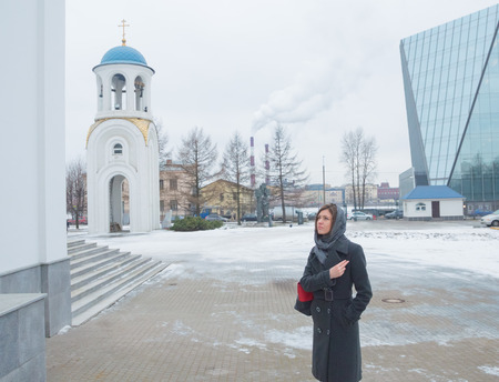 baptized: baptized standing in front of the Orthodox Church, a believer, a girl in a headscarf.
