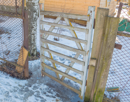 in the winter an old wooden gate with mesh fence netting.