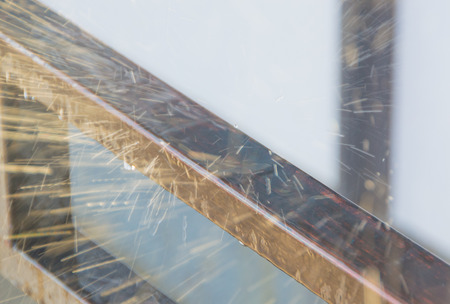 rain drops are broken on a metal railing in a spray of reflecting sunlight. Imagens