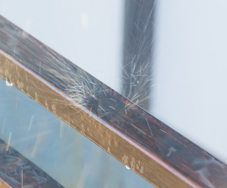 on the background of sunlight on metal railing in a spray of broken water. Imagens