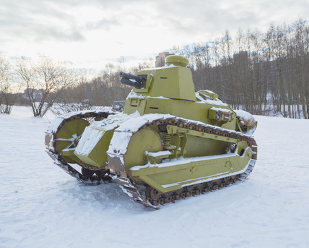 in winter, a flamethrower tank of world war II stands on a hill.