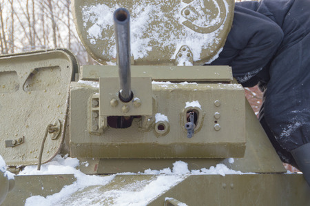 the mechanic-driver of Russian tank t-60, prepares a turret gun.