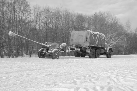 hitched: white and black, truck hitched to the artillery gun of the second world war.