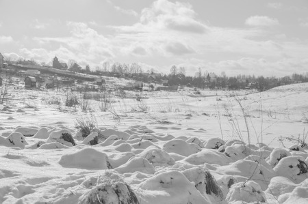 black and white, in the winter the river and the village on the slope of the bright day.