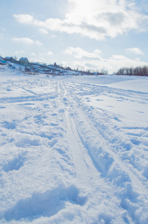 in winter the frozen river with traces trails bright day.