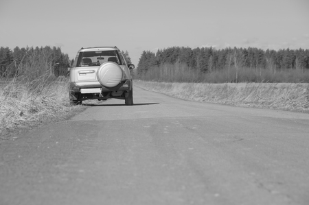 black and white, on a country road is a SUV car. 版權商用圖片