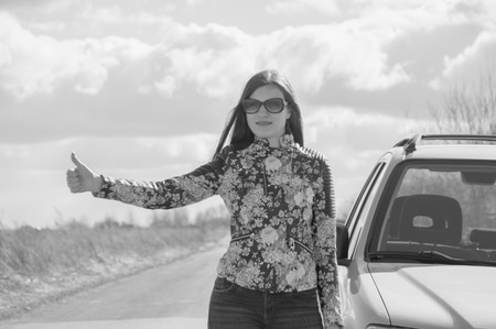 black and white, raising the thumb a beautiful girl stops the car.