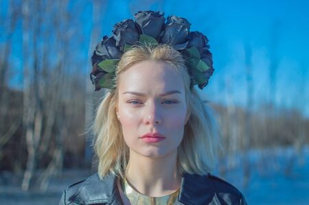 girl with a wreath of black flowers, closeup. Imagens